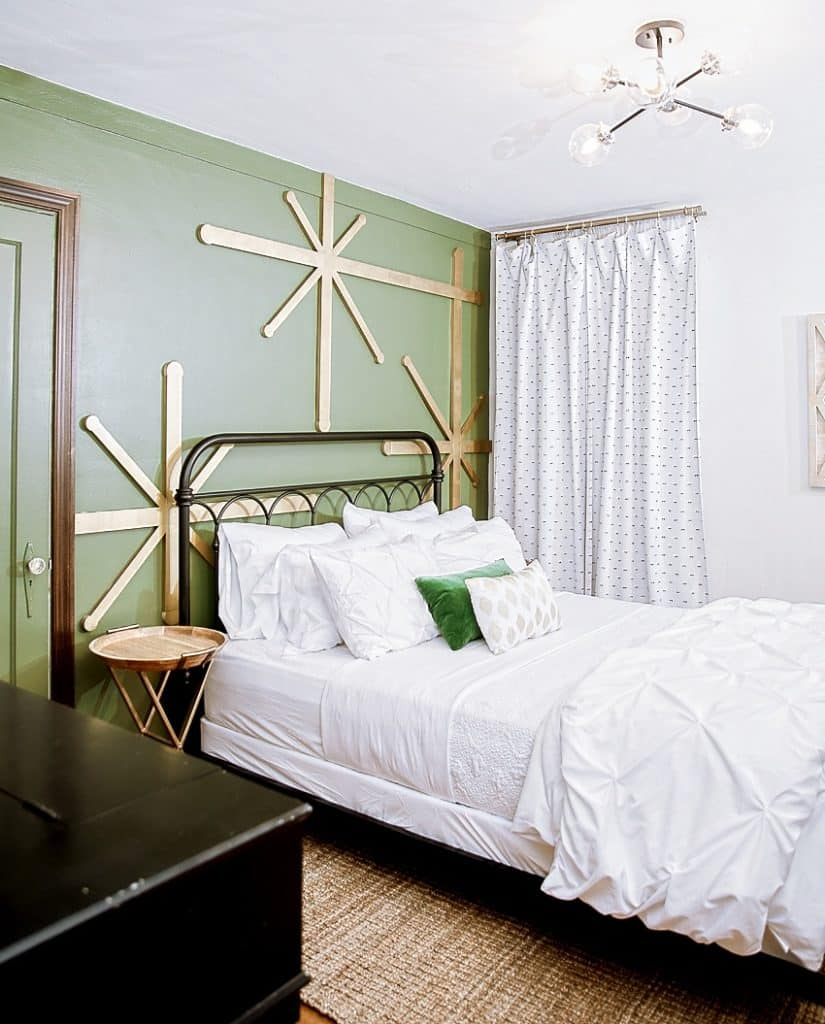 Bedroom with green wall, large gold stars, and a Queen size bed with white bedding on a sisal rug
