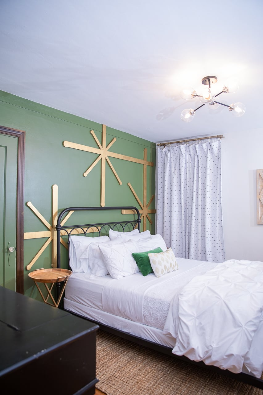 Green walls with giant gold stars and a wrought iron bed with white bedding on a sisal rug.