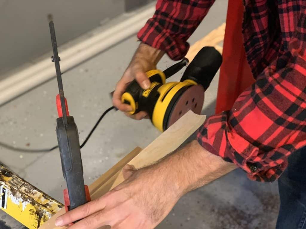 Orbital sander sanding a piece of wood