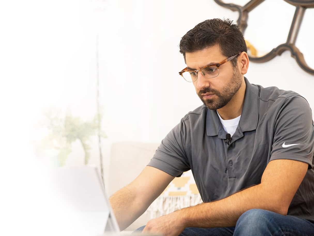 Nestr Founder Nick wears a grey polo and looks at his laptop
