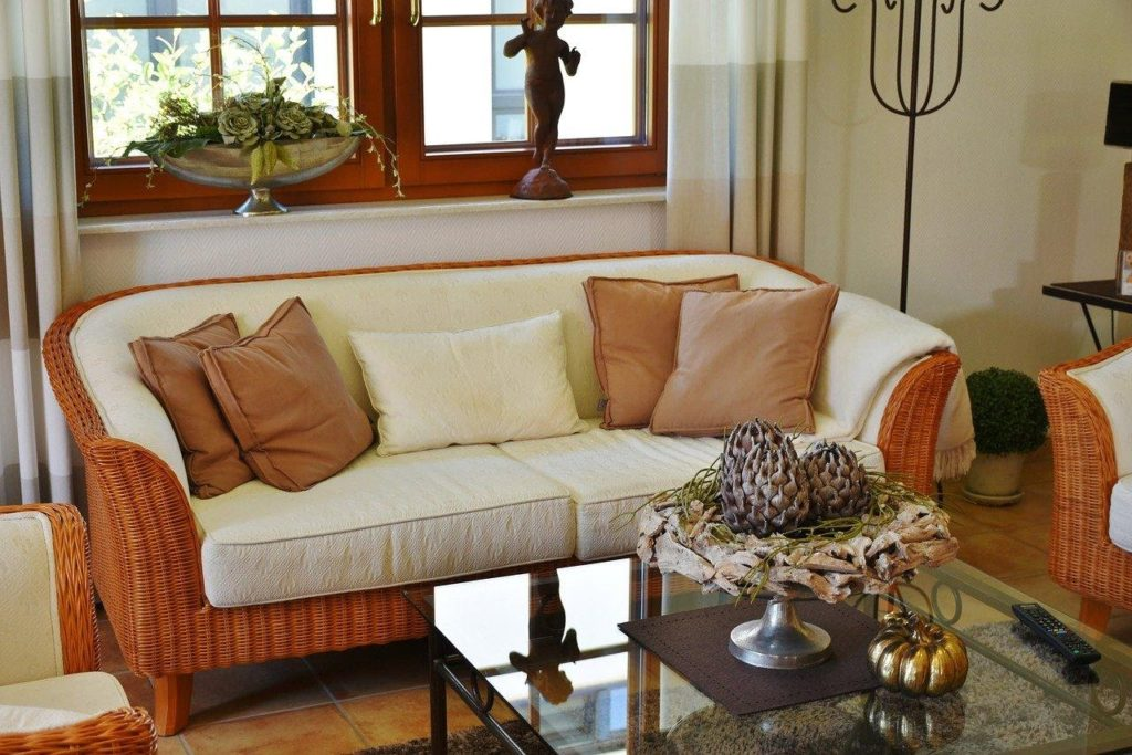 A cozy orange couch is a great place for guests to read and relax.