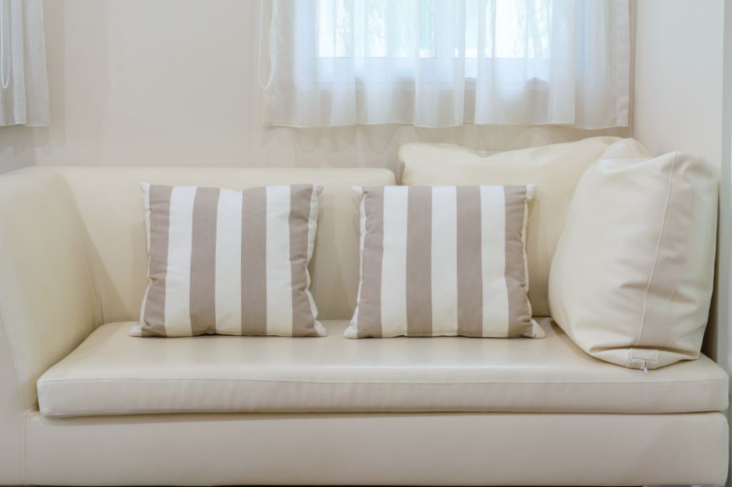 throw pillows on a white leather couch