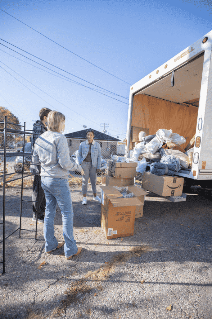 people waiting by the truck with boxes