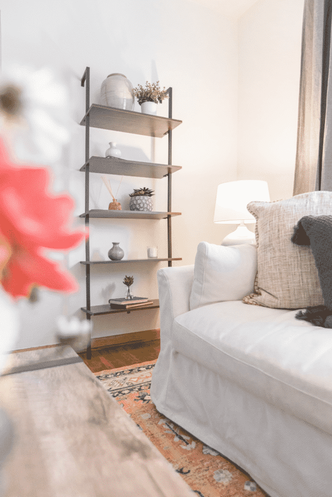 A living room with a white couch and gray shelves covered in pots and plants.