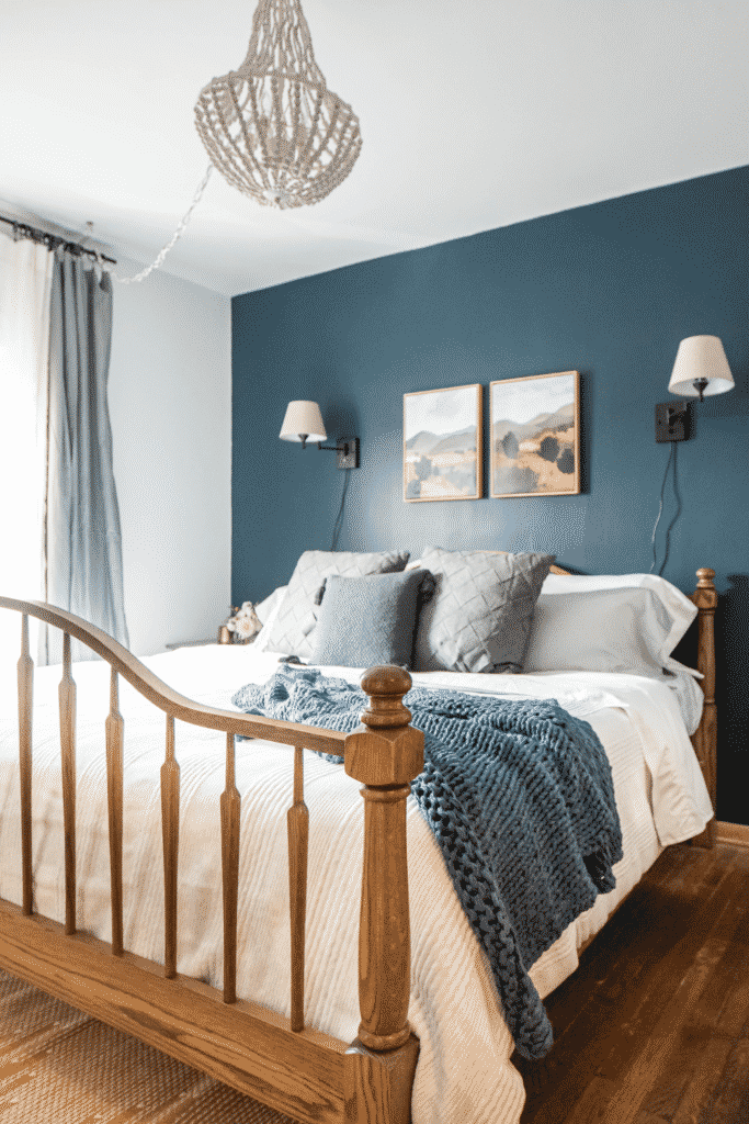 A bedroom with blue walls, hanging lamps, and a freshly-made bed.