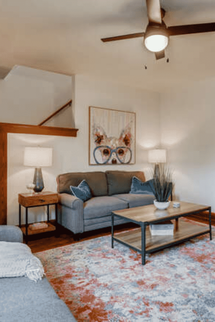 A living room with a ceiling fan light, couches, coffee table, and a dog painting.