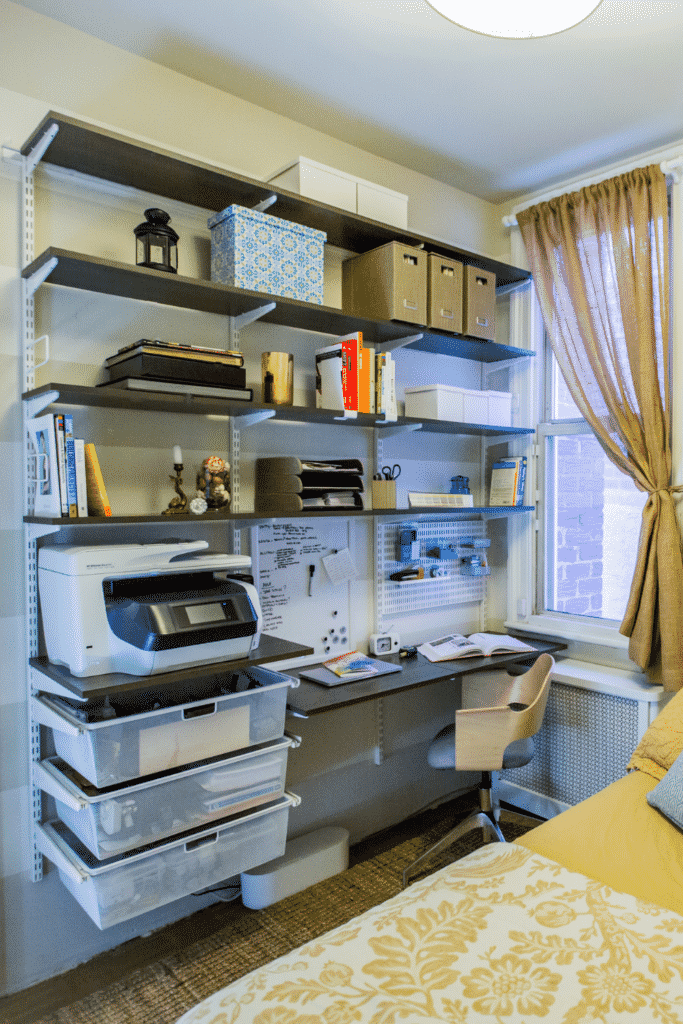 Several wall shelves on the side of a bedroom that serves as an office space.