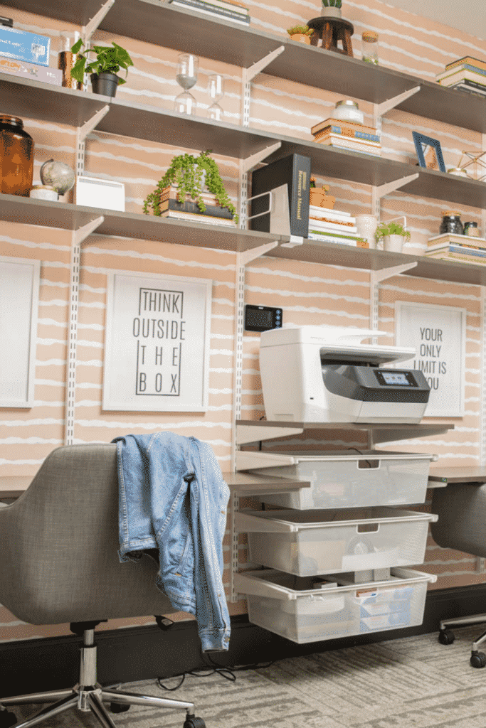Wall shelving above desks holding up a printer, books, and plastic storage containers.