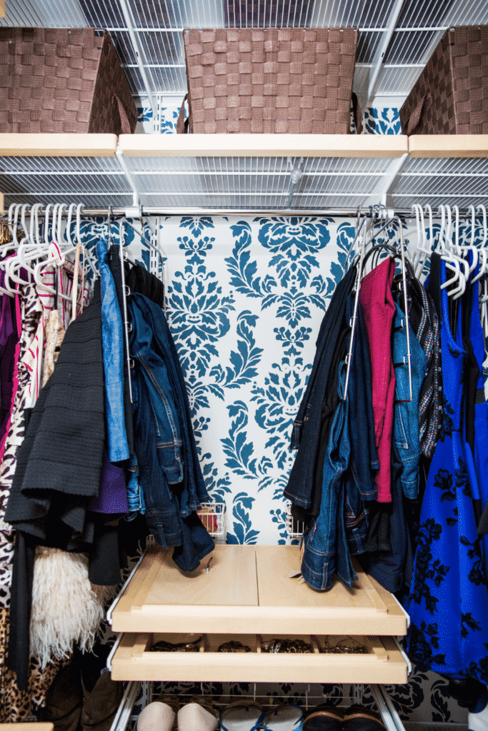 A closet with a shoe organizer and several coats and dresses hung up.