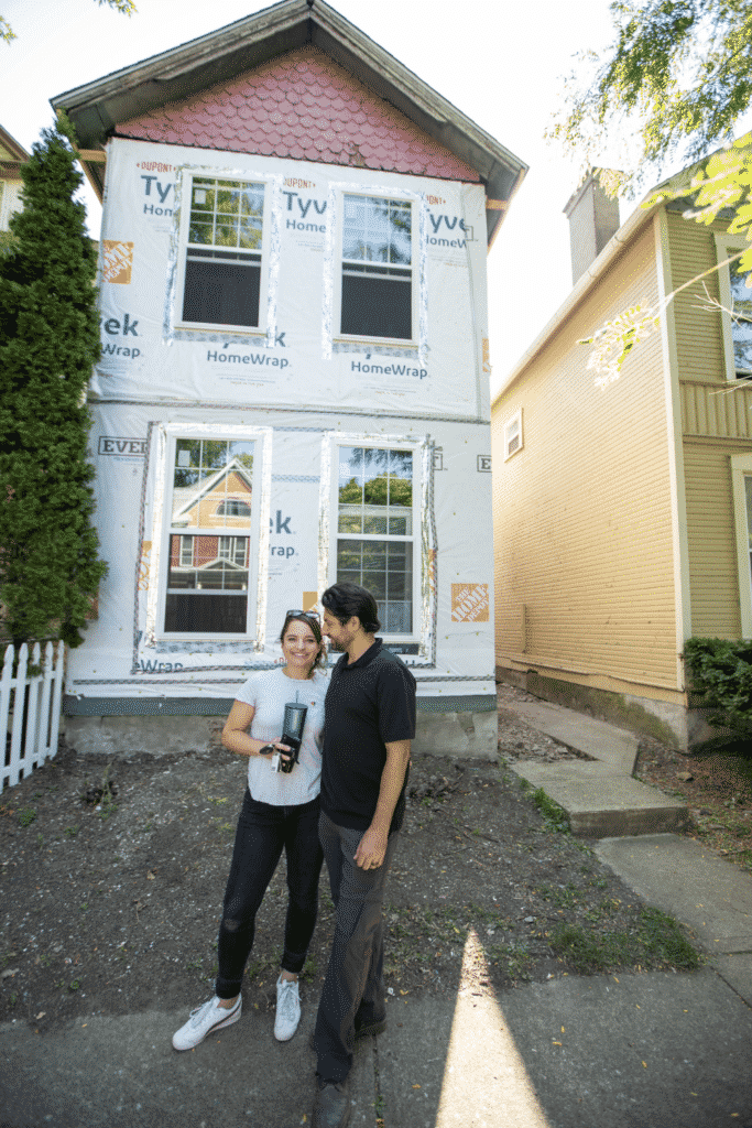 Two people standing in front of a house under construction.