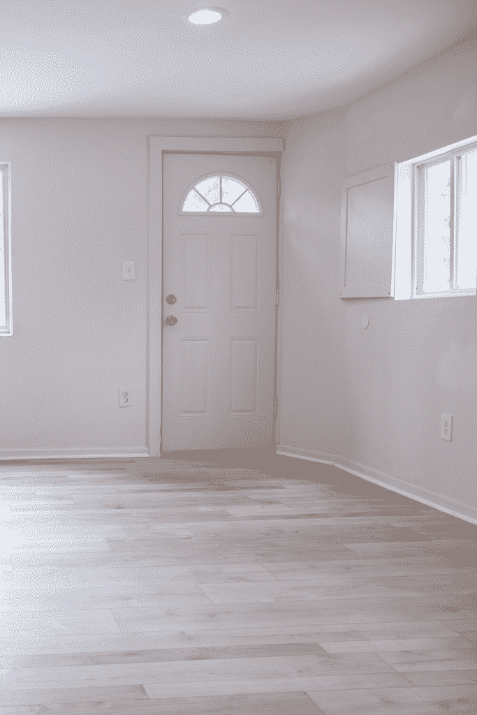 A white door leading into an empty apartment entryway.