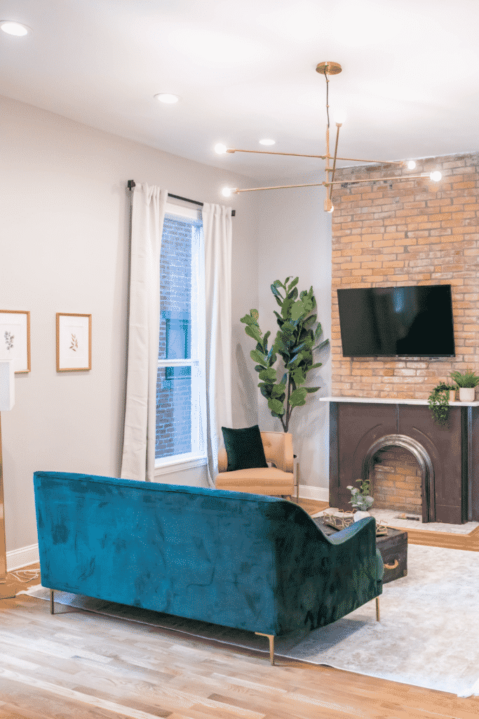 A living room with a blue-green couch, brick fireplace, and flat-screen TV.