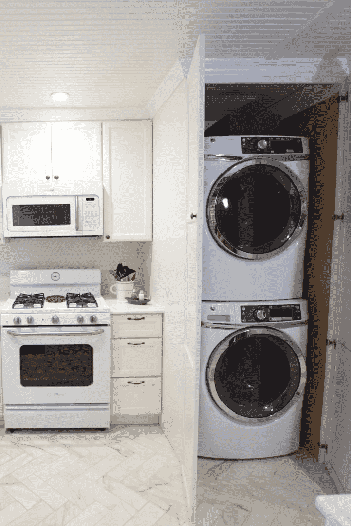 A kitchen with a white stove, oven, and microwave, next to a closet with a stacked washer and dryer.