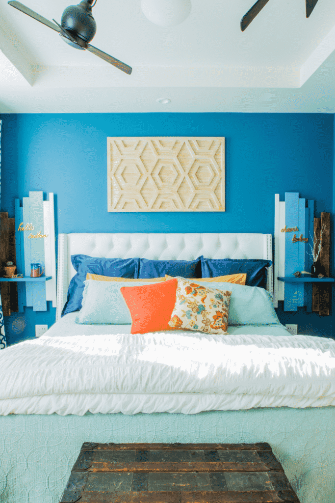 A blue painted bedroom with a colorful bed and an old, wooden chest.