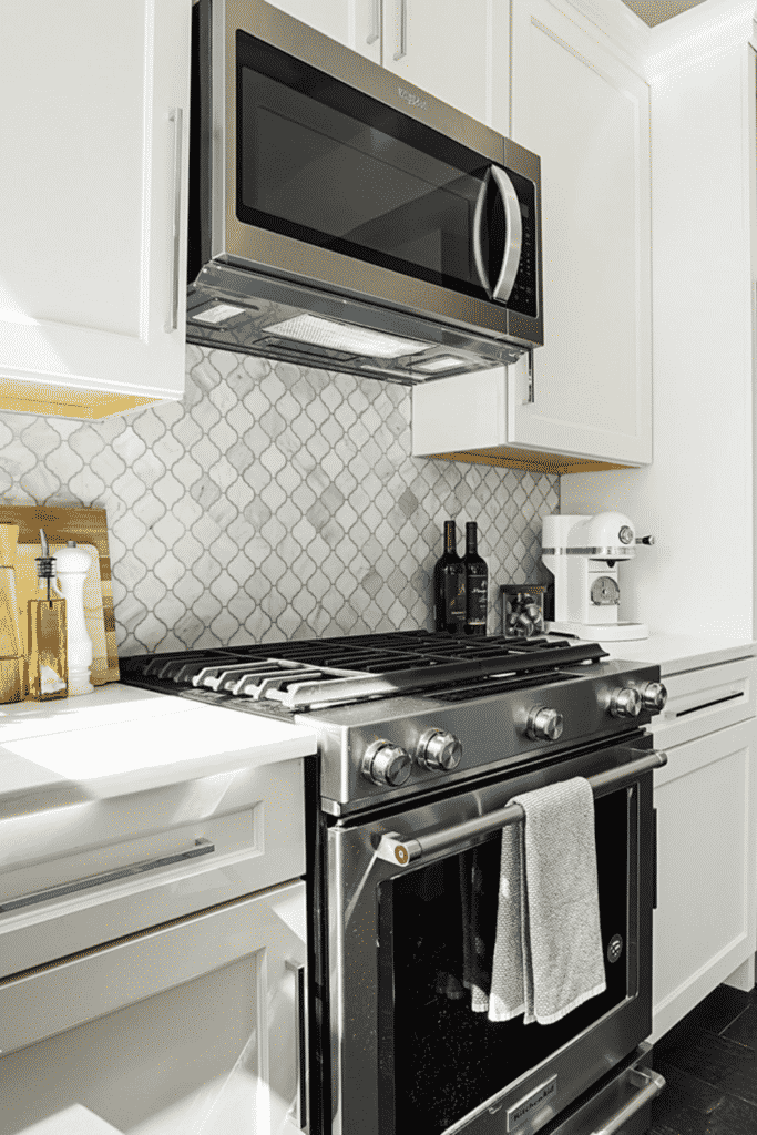 A kitchen oven and stove with an overhanging microwave and white cabinets