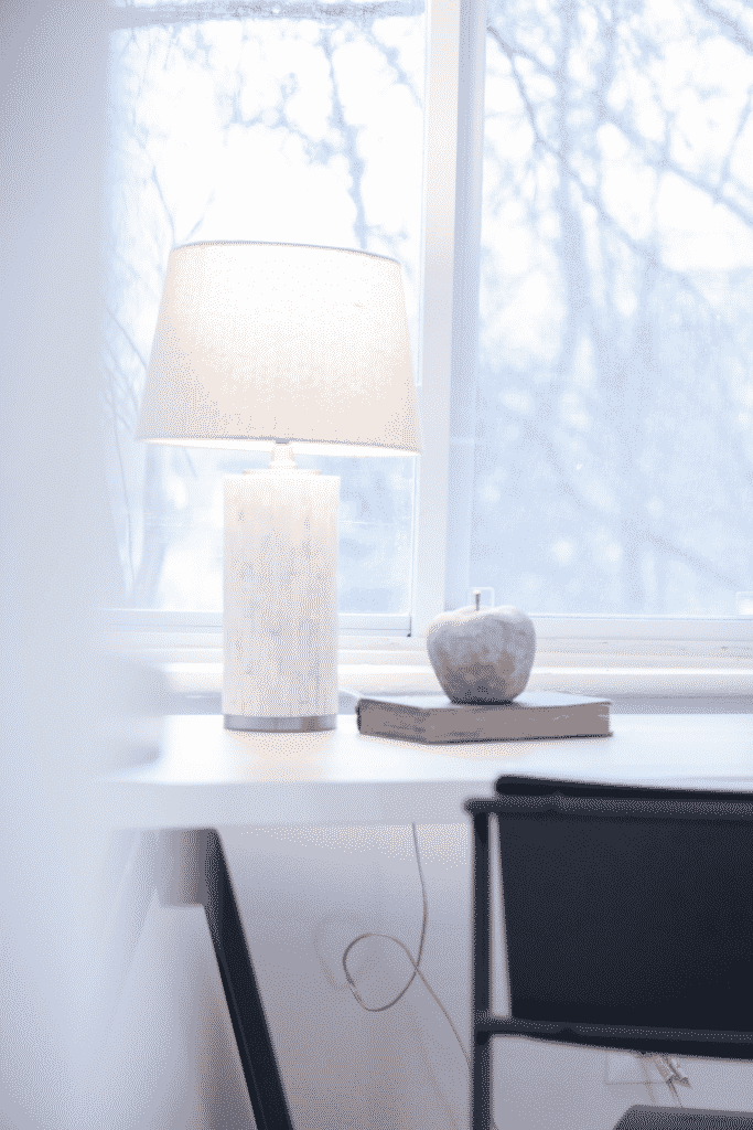 A desk, chair, and white lamp in front of a large window.