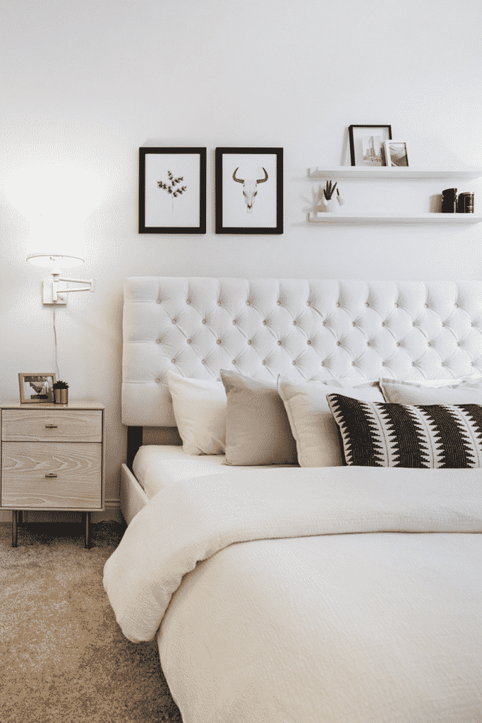A bedroom with a white bed and wooden nightstand.