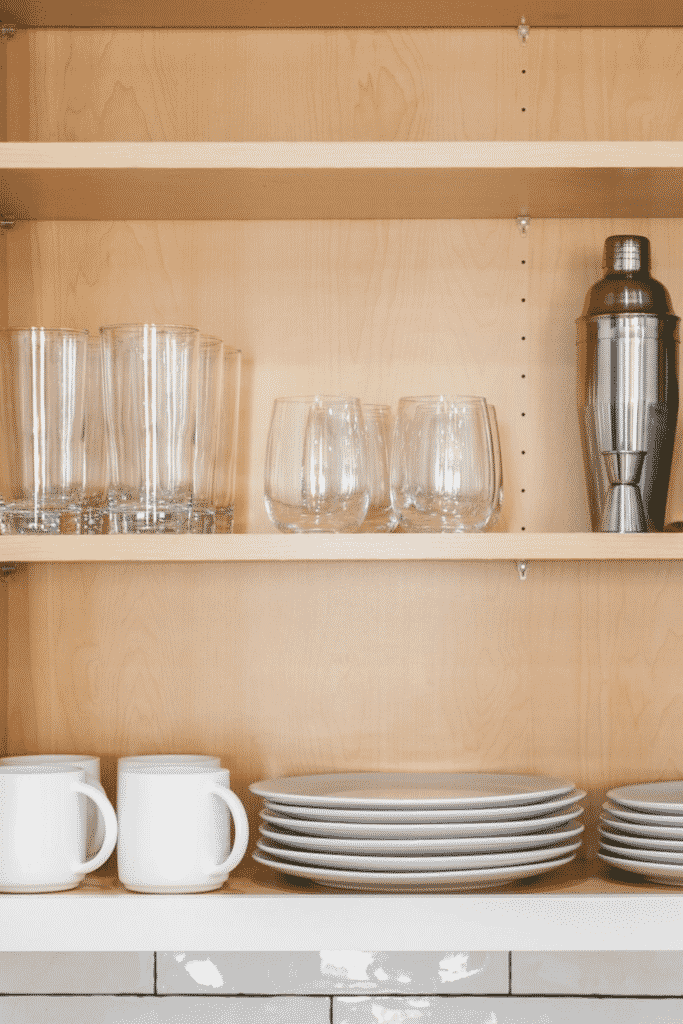 Cupboard shelves of glasses, plates, and coffee cups
