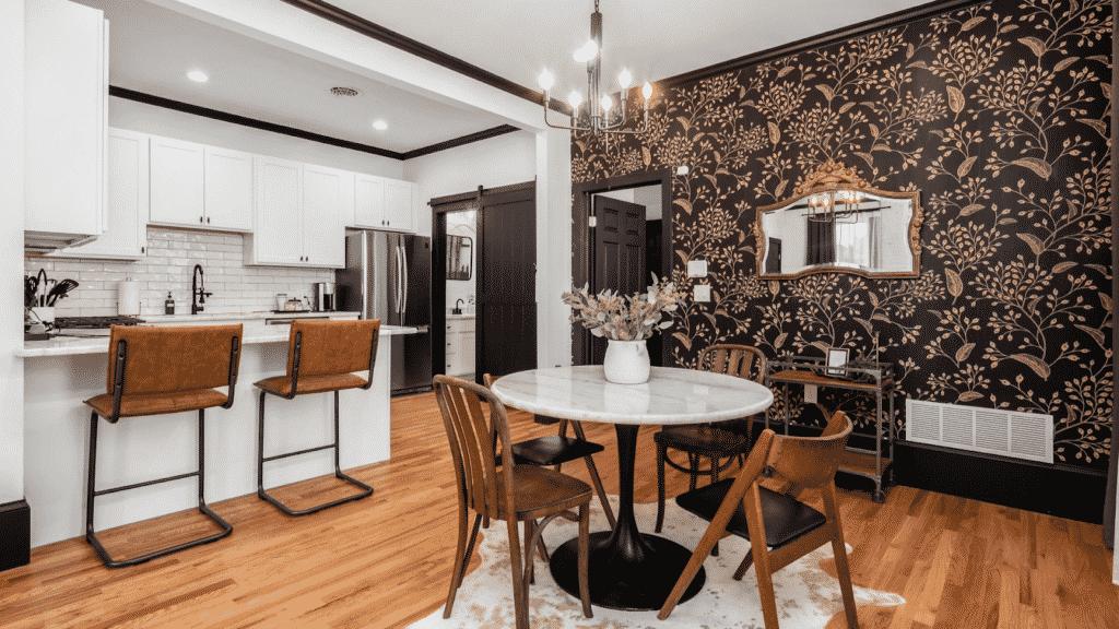 View of elegant and polished kitchen and dining area with accent wall